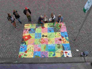 Brigitta Arnold präsentiert das Puzzle der Pirnaer Kinder vor dem Rathaus